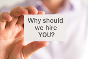 Closeup on businessman holding a card with WHY SHOULD WE HIRE YOU ? message, business concept image with soft focus background