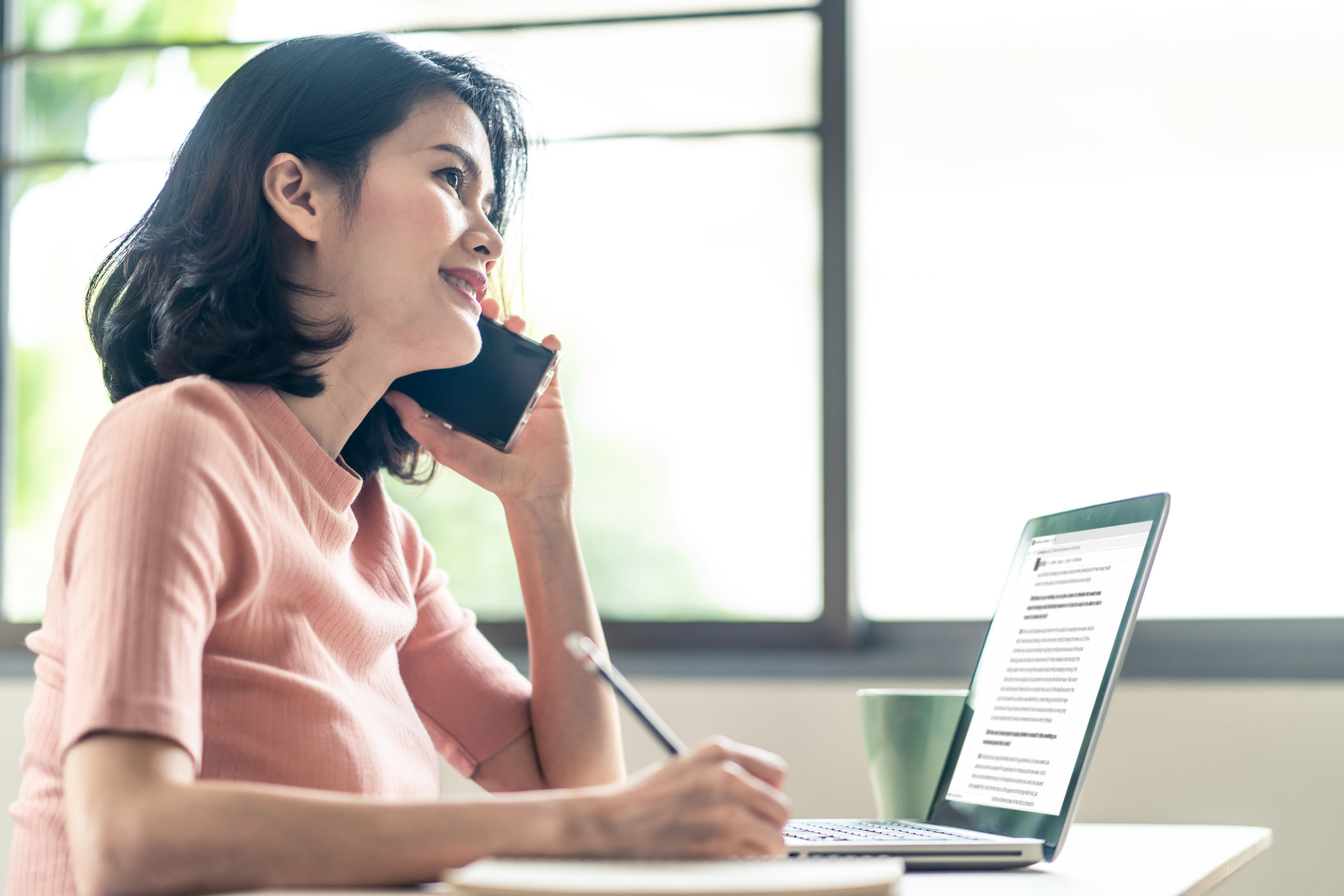 Asian young business woman sit and write note in a notebook while talk on phone and open files in laptop. During Coronavirus crisis Covid19 outbreak girl work from home for prevent contract a disease.